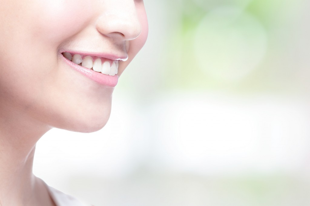 Beautiful young woman health teeth close up and charming smile. with green background, asian beauty